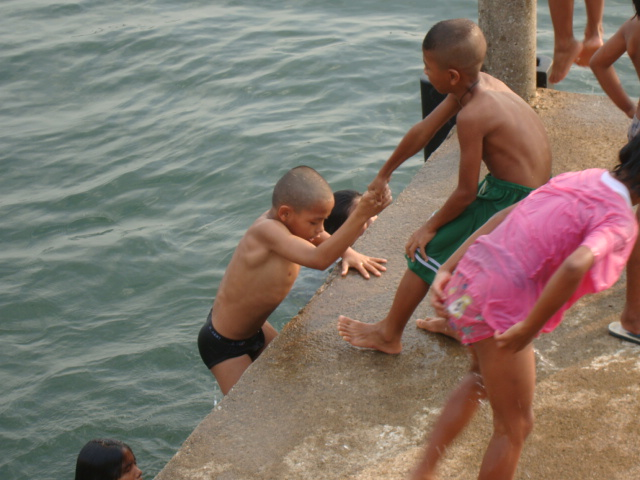 Picture:  Naam's kids help each other in and out of the water.  Sangkhlaburi, Thailand