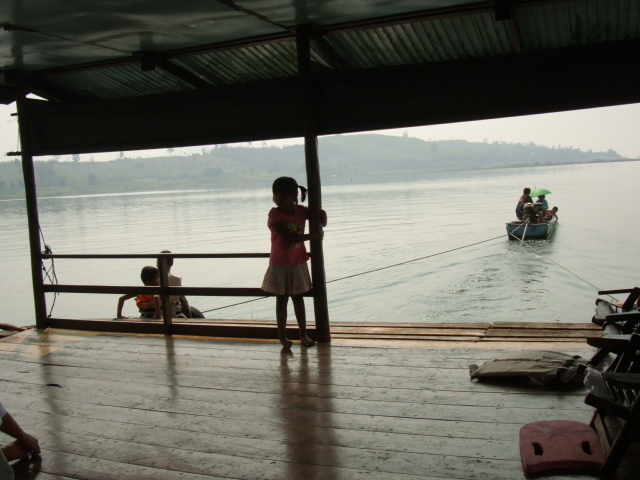 Picture: Long tailed bot tows our barge to the mooring.  Sangkhlaburi, Thailand