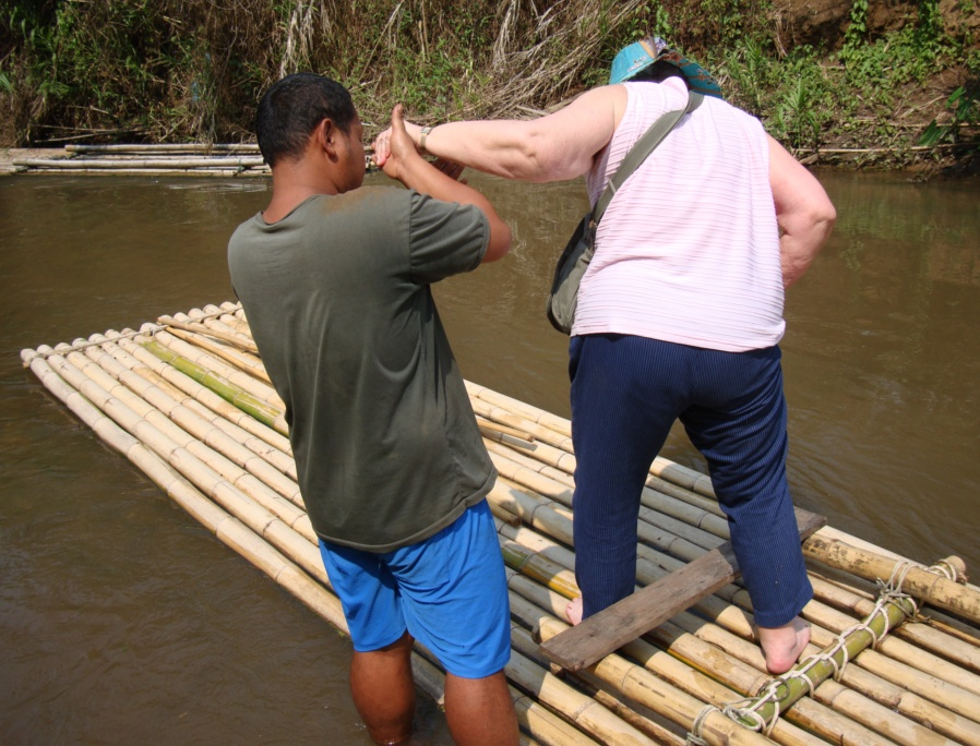 Picture: ya gotta hand it to Pat.  She's game for just about anything. Here she is being helped onto the bamboo raft.