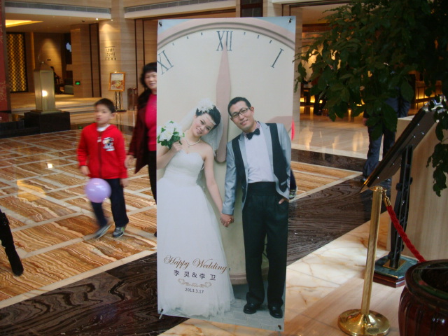 Picture:  The bride and groom, but not our bride and groom, life sized poster on display in the lobby of the Wuxi Gloria Grand Hotel, Wuxi, China