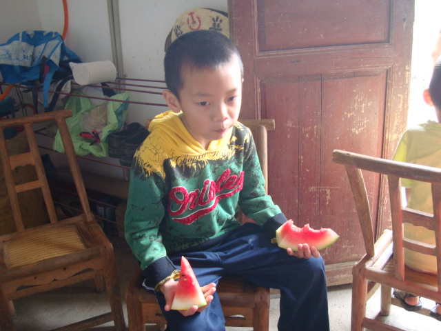 Picture:  Boy with slices of watermelon, Shuibian, Jiangxi, China